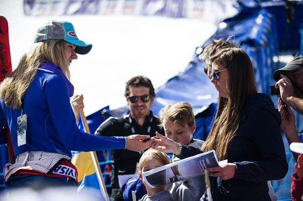 Mikaela Shiffrin signs a poster for a fan at the World Cup finals on Sunday.