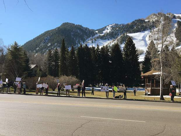 Anti-Trump protesters line Main Street in Aspen in front of Paepcke Park in Aspen on Sunday.