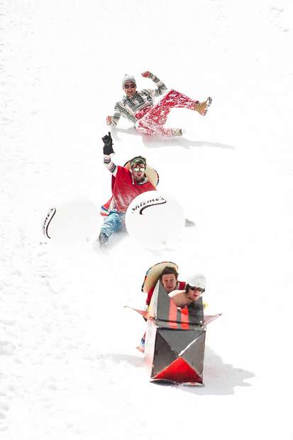 A team slides down the slopes in the Schneetag pond skim for Aspen Highlands closing day on Sunday.
