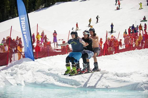 A trio of guys on a single set of skis make their way into the pond skim at Aspen Highlands' closing day on Sunday.