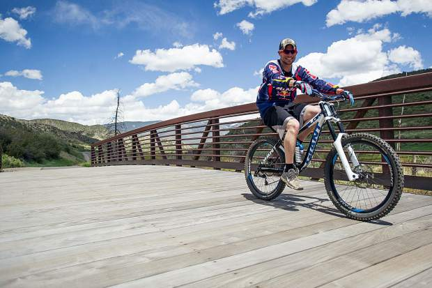 A cyclist rides across the Brush Creek Trail bridge.