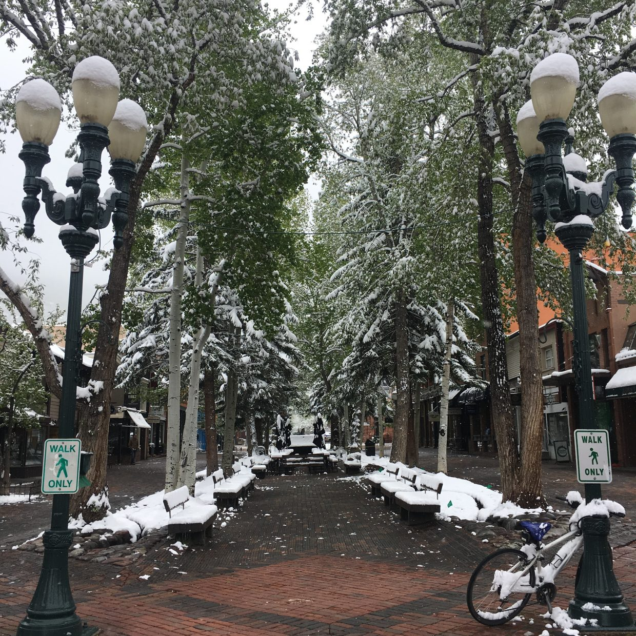 Benches and patio furniture was coated with spring snow Thursday on the pedestrian mall in Aspen.