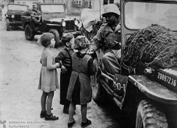 An American soldier passes out candy to local dutch children. Tilly said it was the first time she and her friends had seen a black man.