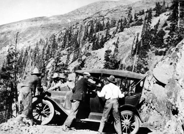 One b/w glossy photograph taken on the west side of Independence Pass in 1922. At least five men are working to turn a car around. Written on the back: