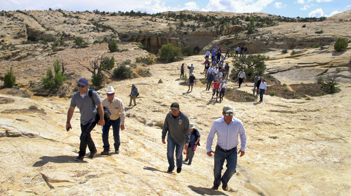Utah state legislators and their staff lead the way for Interior Secretary Ryan Zinke, Utah Gov. Gary Herbert and others in the distance Monday through Bears Ears National Monument near Blanding, Utah.