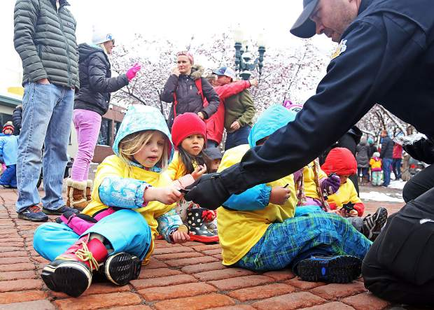 Aspen police officer Andy Atkinson hands out toy police badges to the children during Thursday's Children's Parade in downtown Aspen. The 27th annual event is put on by Kids First in honor of May being the Month of the Young Child.
