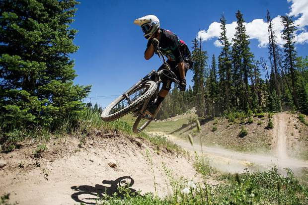 A mountain biker hits a jump on the Valhalla Trail on the Snowmass bike park's opening day June 23.