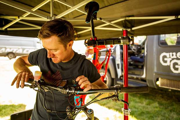 Tyler Henderson of Scott Bikes works on a bike at Snowmass Demo Days on Friday.