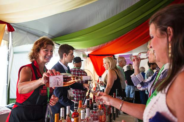 A patron receives a glass of wine in the Spanish tent on Friday for Food and Wine.