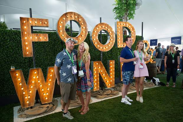Couples pose in front of the Food and Wine lights at the first Grand Tasting of the Food and Wine Classic in Aspen on Friday.