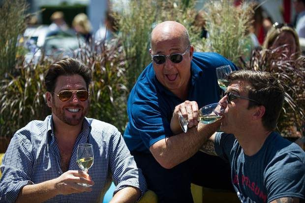 Top chefs left to right Scott Conant, Andrew Zimmern, and Hugh Acheson share a laugh between the tents at the first Grand Tasting of this year's Food and Wine Classic in Aspen on Friday.