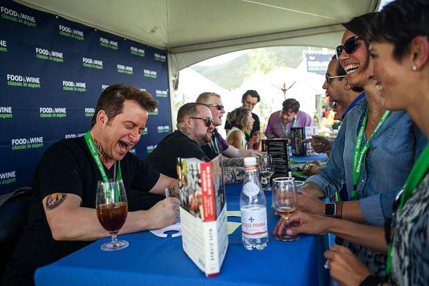 Top chef Mark Oldman has a laugh with fans as he signs autographs at the first Grand Tasting of this year's Food and Wine Classic in Aspen on Friday.