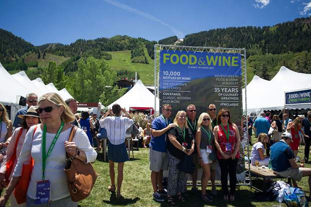 A group poses for a picture from the American Express photobooth for the first Grand Tasting of this year's Food and Wine Classic in Aspen on Friday.