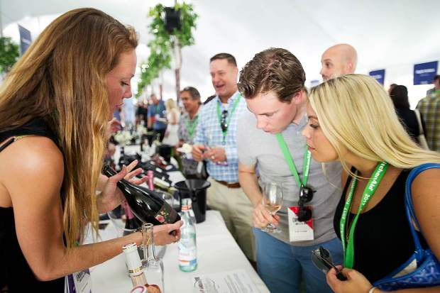Holland residents Meredith Stark and Camille Oostwegel, center, get shown a bottle from Impatience Rose by Kimberli Burns at the first Grand Tasting for Food and Wine in Aspen on Friday.