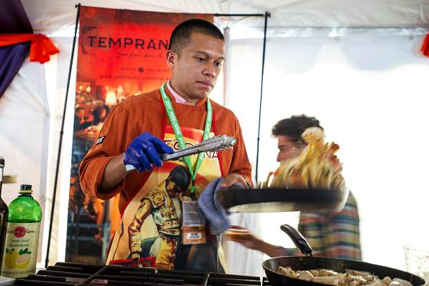 Basalt restaurant Tempranillo's chef Elmer Mira tosses calamari into the air in one of the tents for the first Grand Tasting of this year's Food and Wine Classic on Friday in Aspen.