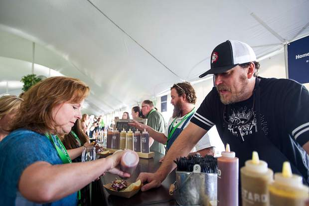 Chef Chris Lanter of Home Team BBQ explains the different sauce selections for their sliders at the first Grand Tasting of Food and Wine on Friday.