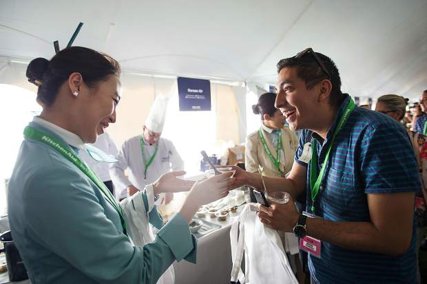 A patron gets a Korean Air dish Friday at the first Grand Tasting at this year's Food and Wine Classic in Aspen.