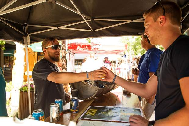 Devin Fielding of Aspen Brewing Company delivering beer to an attendee at the Snowmass Rendezvous Craft Beer Festival on Saturday.
