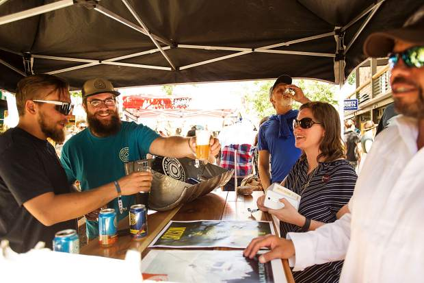 Jacob Dunaway of Aspen Brewing Company delivering beer to an attendee at the Snowmass Rendezvous Craft Beer Festival on Saturday.