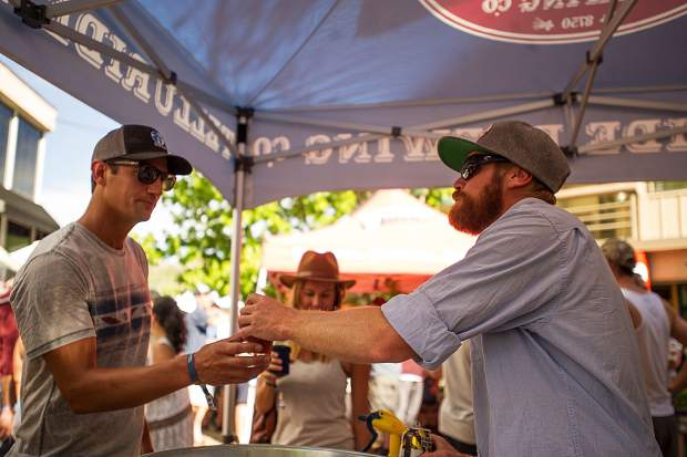 Charlie Ingram of Telluride Brewing Company serves a patron at the Snowmass Rendezvous Craft Beer Festival on Saturday.