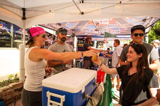 Sidney Brightwell receives a beer from Amy Brumenschenake of the Hideaway Brewery from Winter Park at the Snowmass Rendezvous Craft Beer Festival on Saturday.