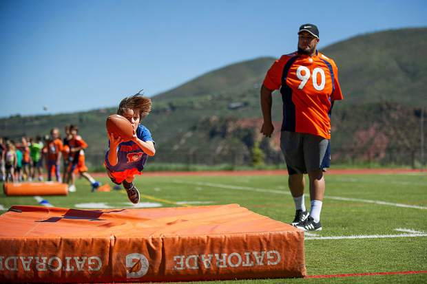 Ethan Ringer, 11, leaps onto a crash pad after catching a throw from Broncos' player Kyle Peko, right, on Aspen High School's football field on Saturday.