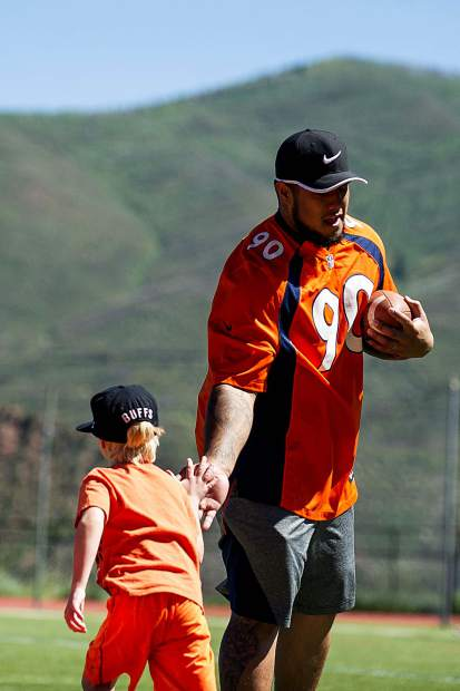 Broncos' player Kyle Peko high fives Rusty Lawson, 6, after completing a football drill Saturday morning at Aspen High for a kids' camp.