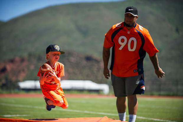Broncos' player Kyle Peko throws a successful catch to Rusty Lawson, 6, during a football drill Saturday morning at Aspen High for a kids' camp.