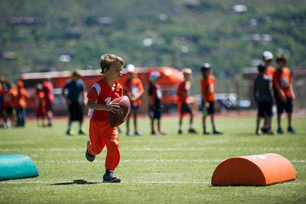 Keenan Ringer, 6, runs through one of the drills at the Bronco's camp on Aspen High School's football field Saturday morning.