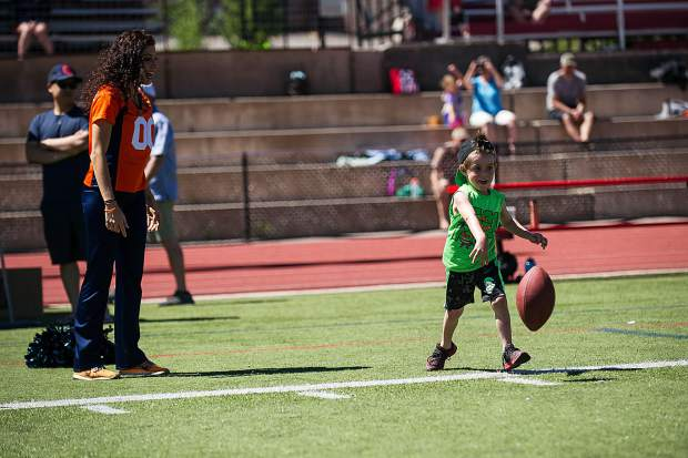 Jack Hunsberger, 5, spikes the football at the Broncos' football camp held at Aspen High School on Saturday.