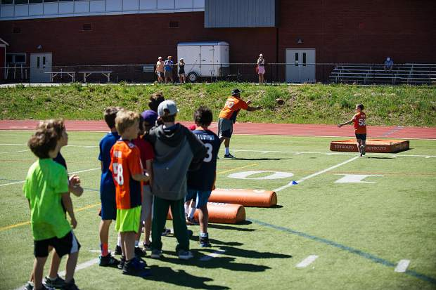 Kids line up for a football drill at a Broncos kids' camp held at Aspen High School Saturday.