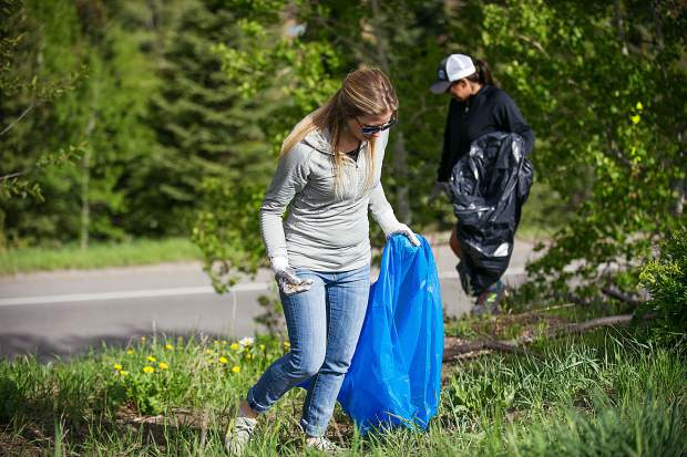 Virginia McNellis picking up trash on a trail near the upper parking lots for Snowmass clean up day on Friday..
