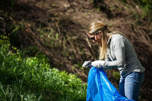 Snowmass Tourism marketing director Virginia McNellis collects trash on a trail near the upper parking lots on June 2.