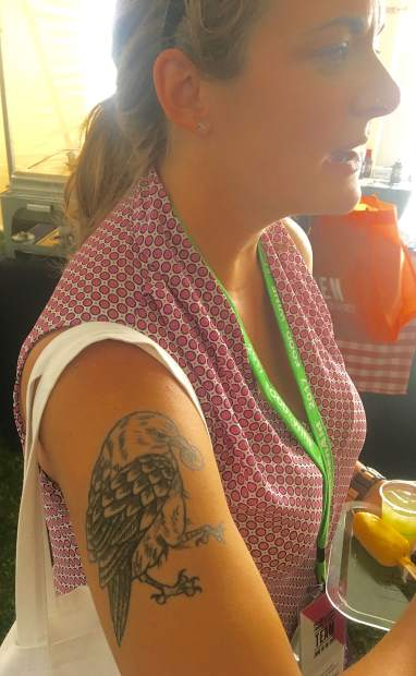 A mystery festivalgoer at the Food & Wine Classic has a bird eating a piece of bread on her upper arm.