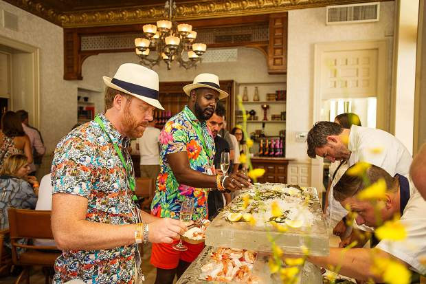Guests pick up various seafood at the raw bar at A Bubbly Brunch hosted at the Hotel Jerome on Sunday.