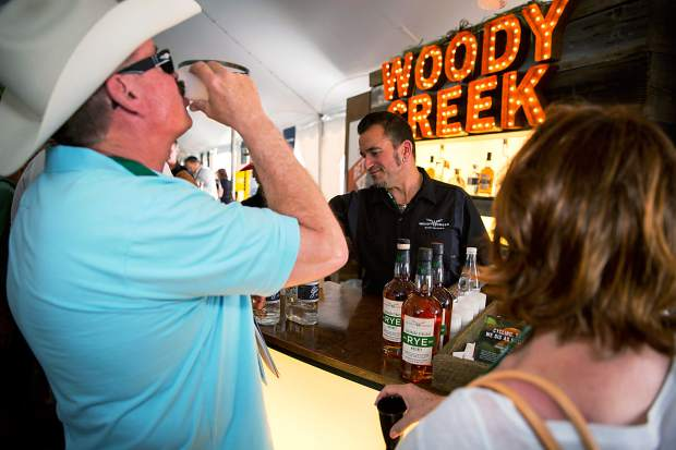 Rick and Bonnie Optiz sample some of Woody Creek Distillery's rye whiskey at the Friday Grand Tasting event. The Spirited Awards' American Bartender of the Year Sean Kenyon is in the background serving up drinks to event-goers.
