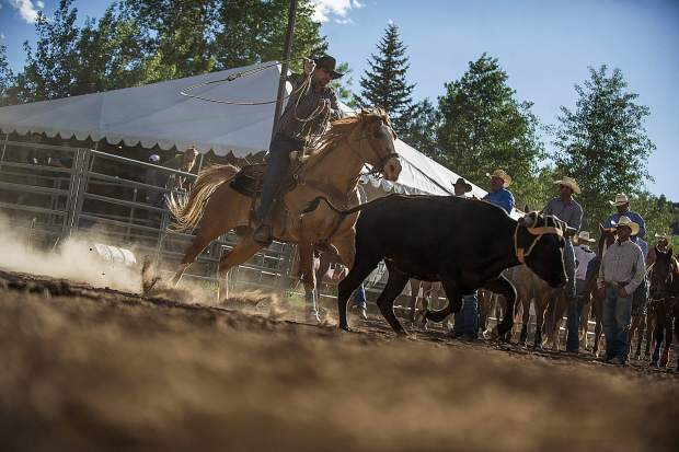 One cowboy from his team chasing a calf in team roping at the first Snowmass Rodeo of the season on June 14.