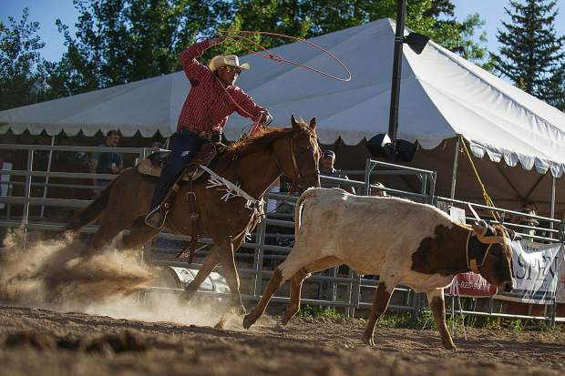 A cowboy chases a calf in team roping at the first Snowmass Rodeo of the season on June 14.