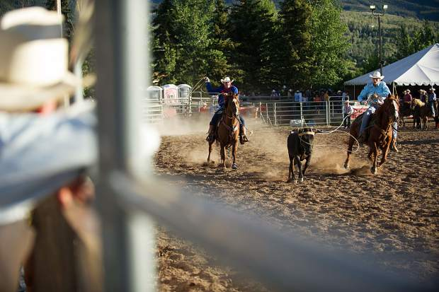Two cowboys chase a calf in team roping at the first Snowmass Rodeo of the season on June 14.