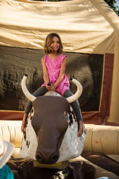 Olivia Pickart, 8, is all smiles and she rides the mechanical bull.