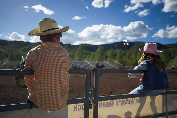 Two young rodeo-goers post up on the fence.