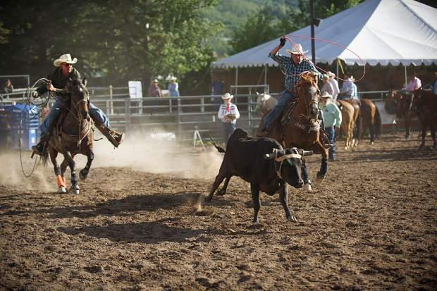 Two cowboys chase a calf during the team roping.