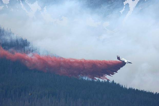 A plane drops fire retardant in Breckenridge, Colo., Wednesday, July 5, 2017. A wildfire has scorched about 60 acres (24.3 hectares) and forced residents from their homes near the Colorado mountain town of Breckenridge. (Hugh Carey/Summit Daily News via AP)