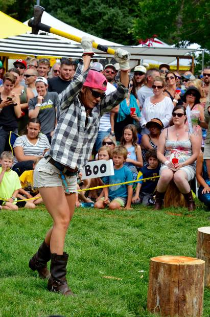Emily Marshall, a veteran of Mountain Fair's wood splitting competition, hacks at a log while being timed against a competitor.