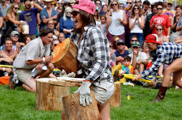 Emily Marshall races to cross the finish line with her split wood during the women's wood chopping competition.