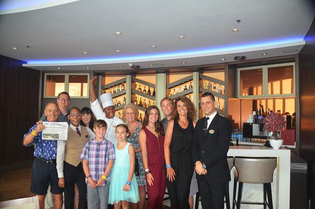 The Kuhn family of Aspen shows off an Aspen Times while on the Royal Caribbean's Harmony of the Seas cruise ship in the middle the Caribbean Sea. Pictured are, from left to right, Niklaus Kuhn (holding The Aspen Times), Andre Kuhn, the head server, Jennifer Kuhn, the chef of Coastal Kitchen, Gertrude Kuhn, Emma Kuhn, Roget Kuhn, Tonya Kuhn and the restaurant manager. In the front are Nik Kuhn and Adrianna Kuhn.