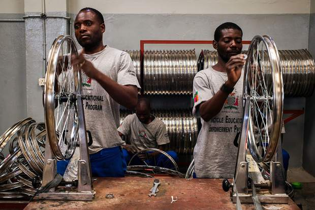 Local Zambians help construct bicycles, which were donated to them through the Aspen Invitational bike ride.