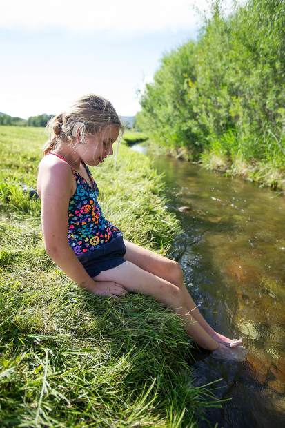 Ava, 13, cools her feet in the creek at their camping spot on Thursday evening.