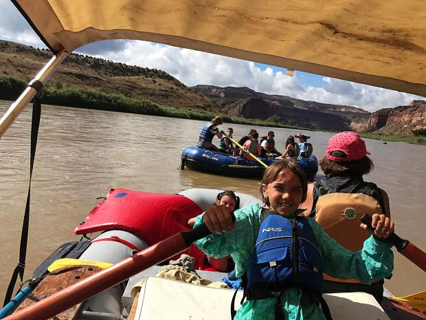 Noal, 12, learns how to oar a raft on the Colorado River during their trip this week.