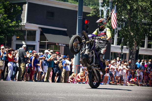 A dirt biker pops a wheelie in the parade on Main Street in Aspen on Tuesday.